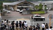 Journalists gather at the main gate of the Tsukui Yamayuri En care centre