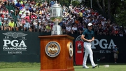 Rory McIlroy walks past the trophy