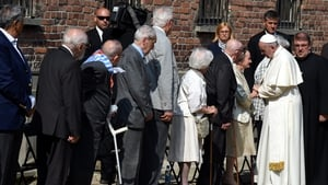 Francis meets with former Auschwitz prisoners in a yard area next to the Death Wall