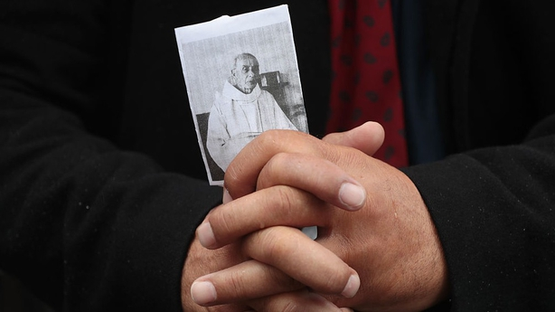 A person holds a picture of the priest Jacques Hamel outside Rouen's cathedral