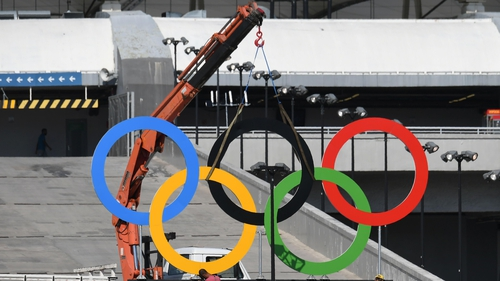 Workers set the Olympic rings outside the Maracana stadium in Rio de Janeiro