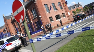 Police stand as they secure the area around a police building in the southern Belgian city of Charleroi following a machete attack