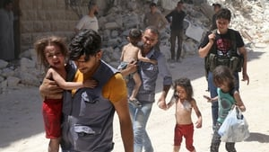 Syrian men carry injured children amid the rubble of destroyed buildings following air strikes on Aleppo