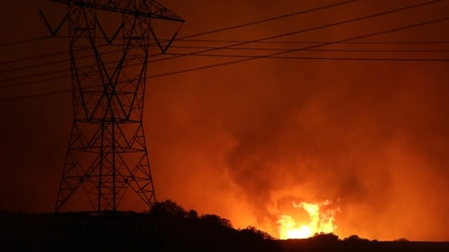 Flames from the Blue Cut Fire threaten power lines north of Los Angeles