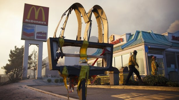 A melted sign from a McDonald's restaurant shows the damage as firefighters check the area after a wildfire swept through Cajon Junction