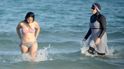 Two Tunisian women swim at a beach near Tunis, one wearing a burkini