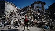 A firefighter stands next to rubble in Amatrice