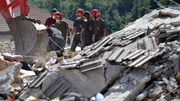 Rescue workers search through the rubble of a destroyed building for survivors in Amatrice