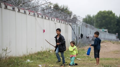 Children play under razor wire at an informal camp close to the E75 Horgas border crossing between Serbia and Hungary