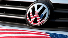 The company and a lawyer for VW dealers announced a tentative settlement at a court hearing in San Francisco, but declined to disclose the amount