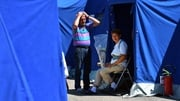 A couple wait outside a tent at a camp for displaced people in Pescara del Tronto