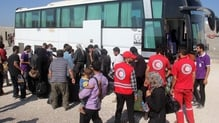 Syrian rebel fighters and their families, helped by volunteers of the Red Crescent, collect their bags from a coach upon their arrival in the rebel-held northwestern city of Idlib