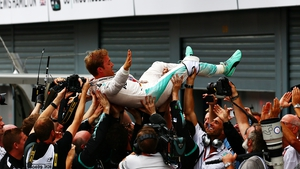 Rosberg is hoisted aloft by his Mercedes team