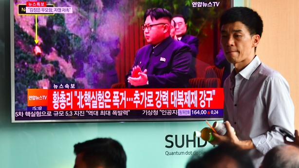 People watch a television news report showing file footage of Kim Jong-Un in Seoul