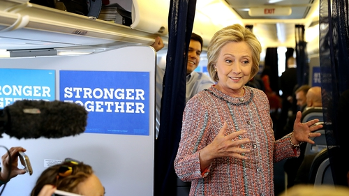 Hillary Clinton speaks to members of the travelling press aboard her campaign plane