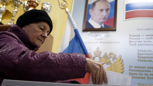 An elderly woman casts her ballot in front of a portrait of Russian President Vladimir Putin at a polling station in Moscow, Russia