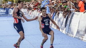 Alistair Brownlee (L) helps his brother Jonny before crossing the line in second and third place during the ITU World Triathlon Championships