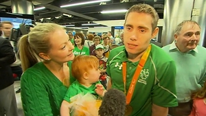 Gold medalist Jason Smyth is welcomed home by his wife and child