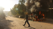 A man walks past a bus set ablaze following a reported air strike in the rebel-held Salaheddin district of Aleppo