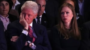 Husband and former US president Bill Clinton and daughter, Chelsea Clinton, listen as Democratic nominee Hillary Clinton speaks during the debate