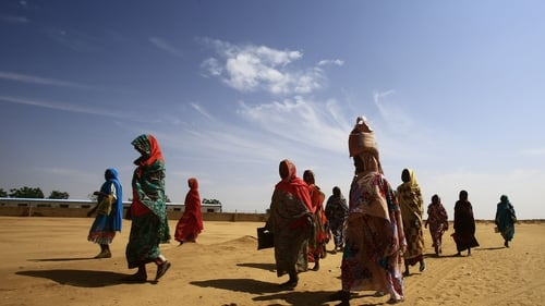 Women walk at the Abu Shouk camp for Internally Displaced People, near North Darfur's state capital