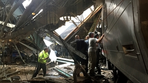 Train personnel survey the NJ Transit train that crashed into the platform