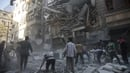 Civilians gather at the site of a government airstrike in Aleppo