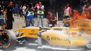 The car of Kevin Magnussen of Denmark and Renault Sport F1 on fire in the pitlane