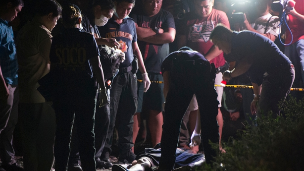 Members of police Scene of the Crime Operative examine a dead suspected drug pusher