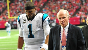 Panthers' Cam Newton leaves the field with the team doctor