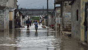 People walk through flooded streets in the Haitian capital
