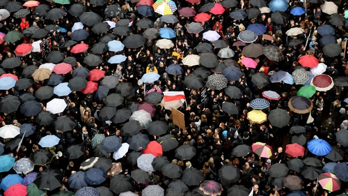 People attend a protest against the proposed law in Warsaw