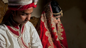 Mohammad Hasamur Rahman, 32, poses for photographs with his new bride, 15-year-old Nasoin Akhter in Bangladesh  last year