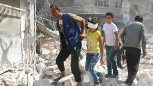 Syrians walk over rubble following air strikes on the rebel-held Fardous neighbourhood of Aleppo