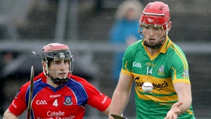 Gort's Michael Mullins hand passes with Cathal Burke close by