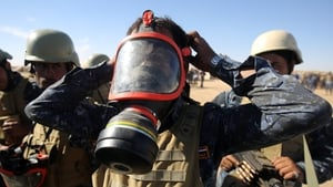 An Iraqi policeman tries on a gas mask outside Mosul