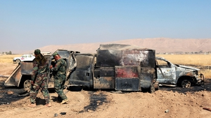 Soldiers inspect a burnt truck used by militants to liberate several villages from the control of IS, east of Mosul
