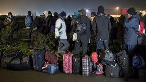 Migrants line up with their possessions ahead of evacuation this morning
