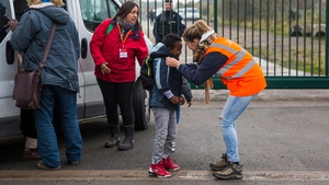 A care worker brings a child to a reception point outside the 'jungle'