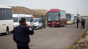 Buses to take migrants to refugee centres across France queue outside a reception point