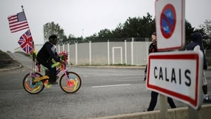 A migrant cycles on a bike with flowers and flags as migrants begin to leave the camp before authorities demolish the site