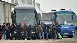 Buses take people from the camp to registration centres