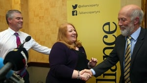 Naomi Long shakes hands with outgoing leader David Ford as her husband Alliance Party's Naomi Long with husband Michael Long looks on