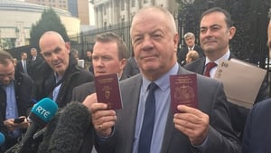 Campaigner Raymond McCord poses outside the court with his new Republic of Ireland passport after the ruling