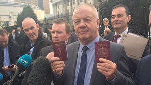 Campaigner Raymond McCord poses outside the court with his new Irish passport after the ruling