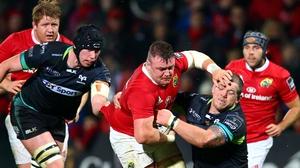 Munster's Dave Kilcoyne is tackled by Paul James of Ospreys