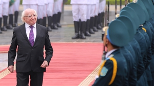 President Michael D Higgins reviews an honor guard during a welcoming ceremony at the Presidential Palace in Hanoi