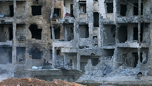 Syrian pro-government forces drive an infantry fighting vehicle past heavily damaged buildings in Aleppo's 1070 district