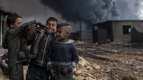 A group of boys play in a street outside their home in front of a burning oil well set on fire by fleeing IS members south of Mosul