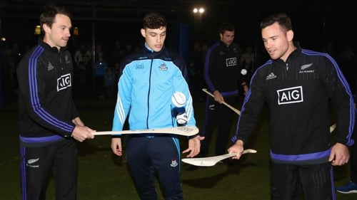 Ben Smith (L) and Ryan Crotty (R) try their hand at hurling under the guidance of Dublin's Eoghan O'Donnell at the AIG Skills Challenge